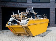 Yellow dumpster with furniture